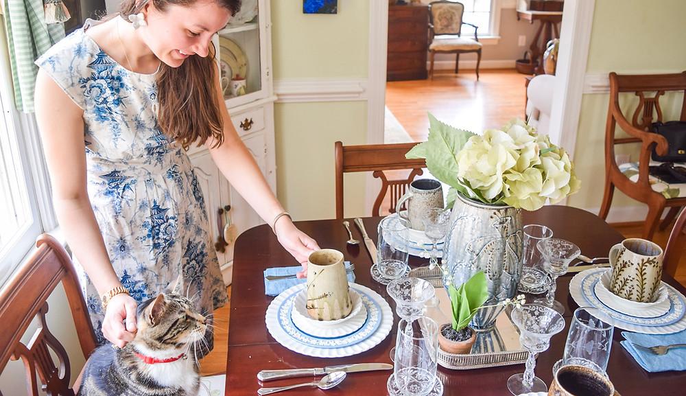 woman-petting-cat-woman-wearing-flower-earrings-woman-wearing-headband-woman-wearing-chinosiere-dress-woman-wearing-floral-print-dress-woman-holding-pottery-mug-pottery-vase-ceramic-mug-table-setting-vintage-table-setting.jpg