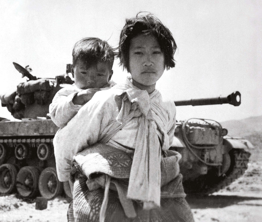 Korean girl tiredly trudges by a stalled M-26 tank, at Haengju, Korea in June 1951 | Photo Credit: Maj. R. V. Spencer.