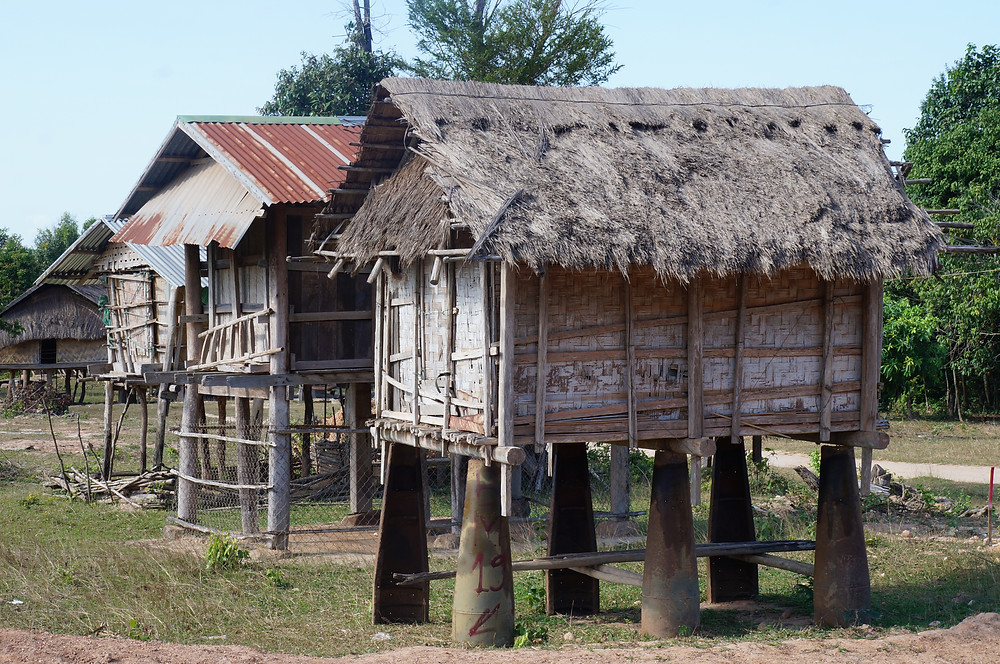 A housing structure in a remote village is raised by remnants of bombs used by the U.S. during the Secret War in Laos | Photo Credit: War Legacies Project staff.