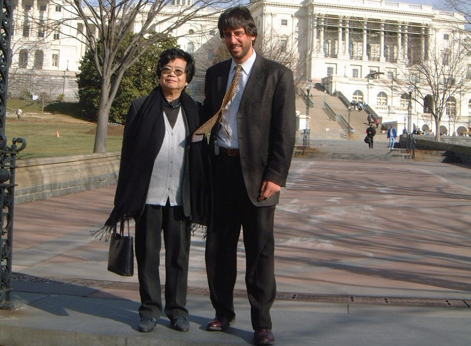 "Plaintiff of a lawsuit filed by the Vietnam Association for Victims of Agent Orange, Phi Phi stands outside of courthouse with lawyer as captured in ""The Last Ghost of War"" (2008), narrated by Kevin Kline, produced by Pham Quoc Thai and Janet Gardner, directed by Ms. Gardner."