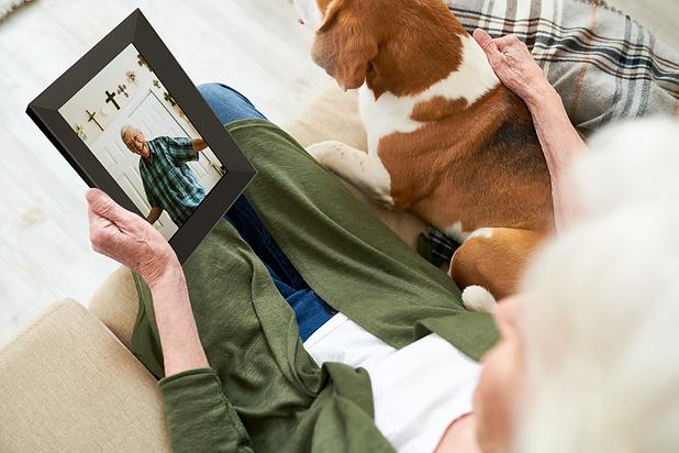 senior-woman-showing-photo-to-dog-U5Z4F2