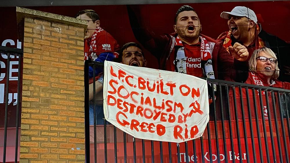 """Een banner op het stadium van Liverpool Football Club gehangen met het opschrift: """"Liverpool Football Club. Built on Socialism, Destroyed by Greed. R.I.P."""""""
