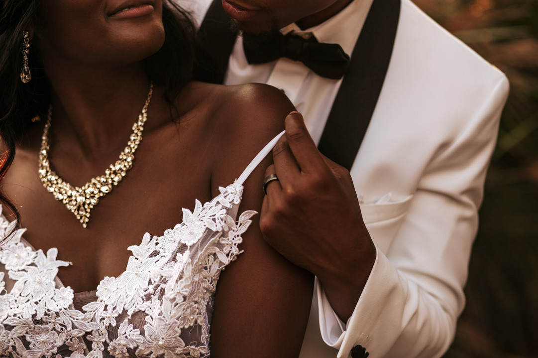 black bride and groom with white tux