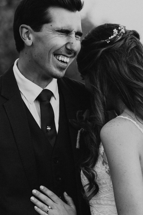 groom in vineyard laughing with bride