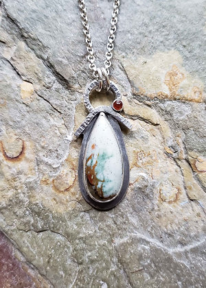 Blues and browns in silver shaped like an angel pendant.