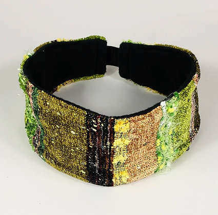 green, brown, and yellow striped woven headband with black lining and elastic band