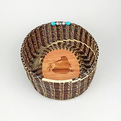 Brown woven basket with light stitching, wooden base with image of native flute player