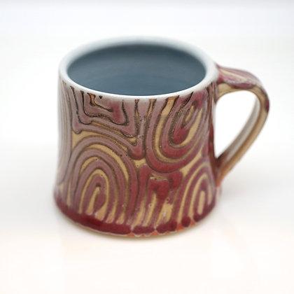 front view, abstract design, burgundy swirls on beige mug