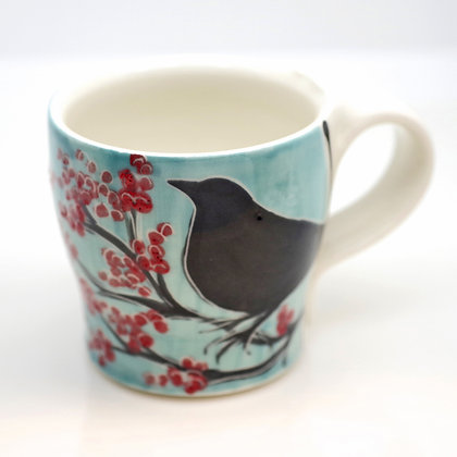 front view, raven with red berries on blue sky, handpainted mug