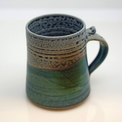 front view, blue and green mug with rust highlights