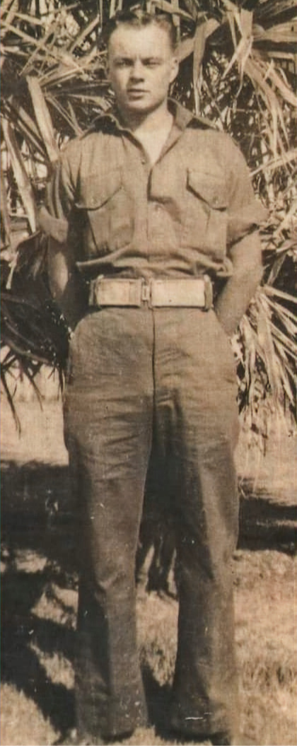 Picture of Noel Frederick South in his late teens or early twenties. Date uncertain.Standing on grass in front of a tree.