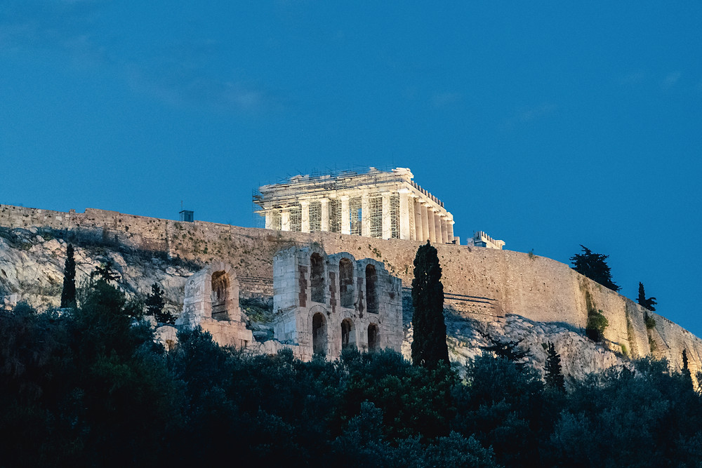 View of the Acropolis in Athens with the Parthenon lit up at night.