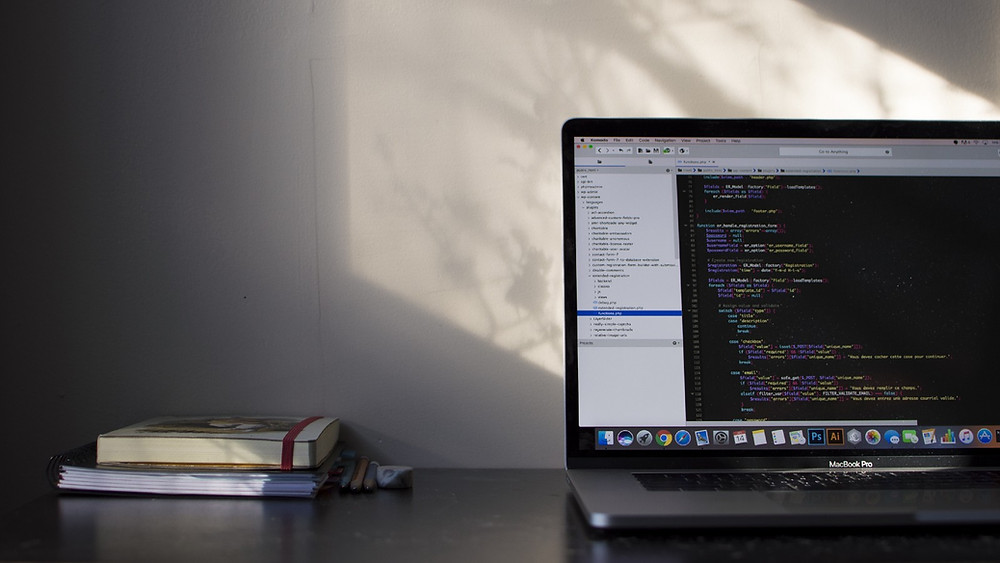 """""""Two books on a desk near a MacBook with lines of code on its screen"""" by Émile Perron on Unsplash"""