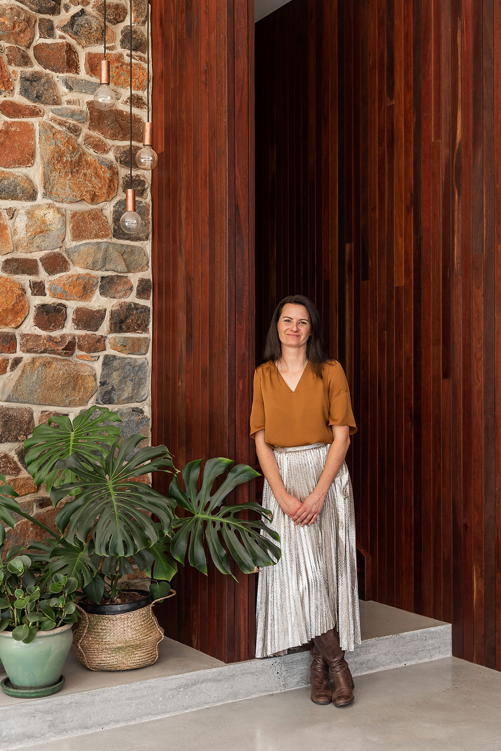 Alice Ostrowski, Director and Wellness Architect, AO Architects, standing by Jarrah cladding to lounge and curved entry wall - Nyaania Creek Darlington Residence