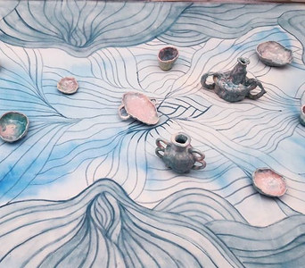 Blue tapestry with ceramic objects