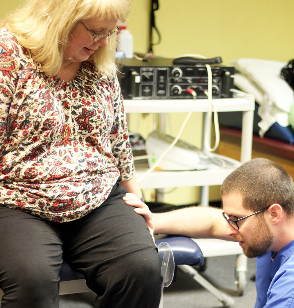 Director of Rehab and physical therapist, Spencer Boothe, measuring a patient's knee at 360 Total Rehab in Flowood, MS.