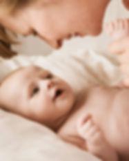 Mutter, die mit neugeborenem Baby lächel