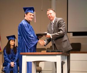Pastor presenting Mich his diploma.