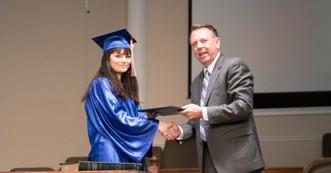 Pastor presenting Raegan her diploma.