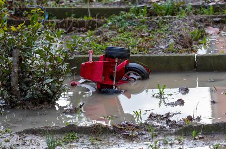 Sogni infranti. Un triciclo coperto dal fango e dall'acqua