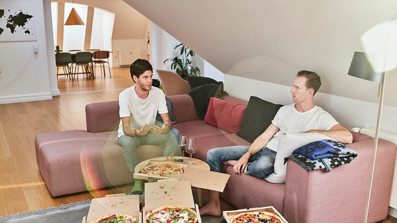 Paul Sephton(L) 28 y.o from South Africa and Tim Aardenburg from the Netherlands sharing pizza and a glass of wine in their shared living room in one of lifeX apartments in the Østerbro neighbourhood in Copenhagen. The apartment is fully furnished by the Danish company HAY.