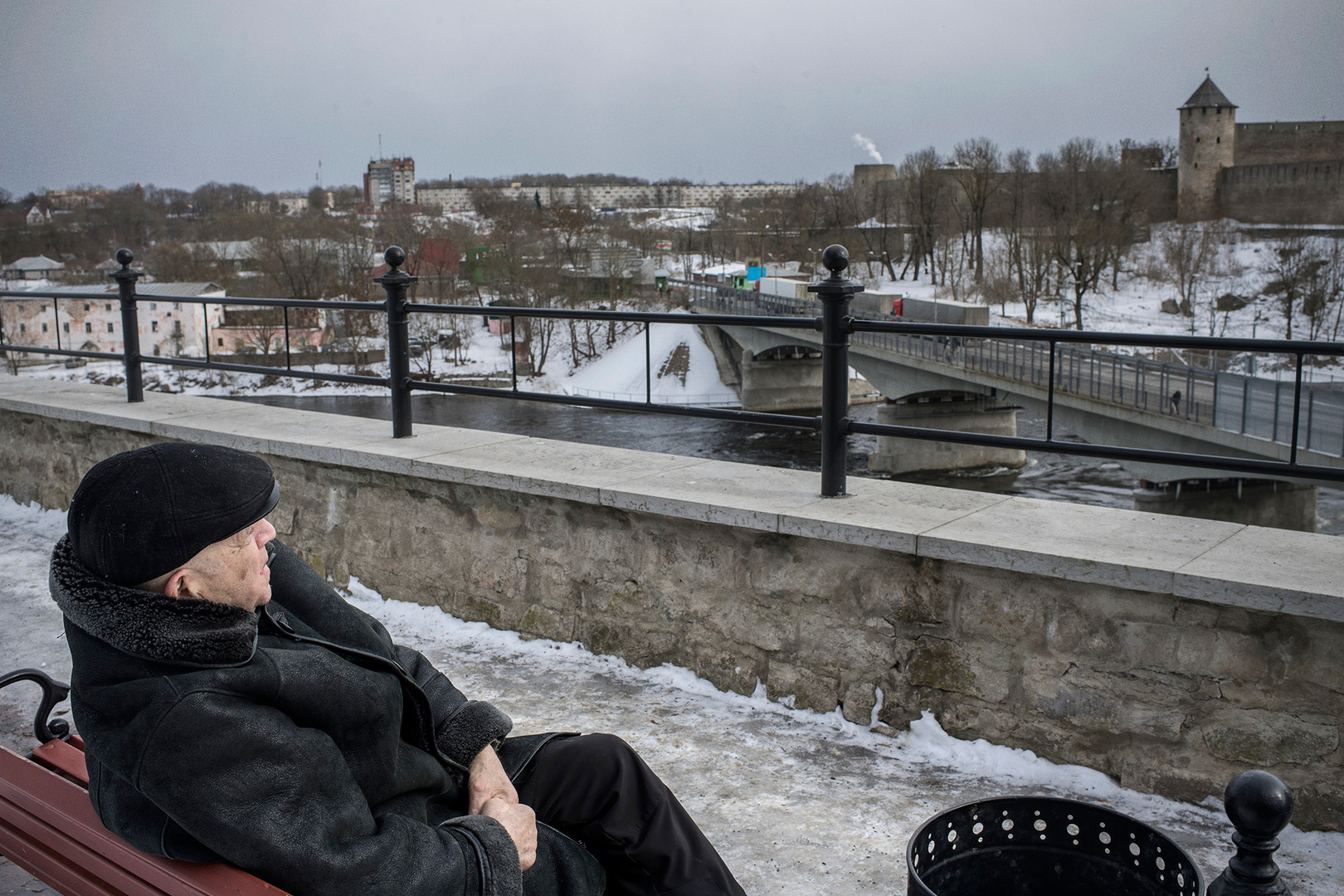 A Russian speaking man is sitting on a bench by the river Narva in the city with the same name. Over the river runs a bridge connecting Estonia and Russia.