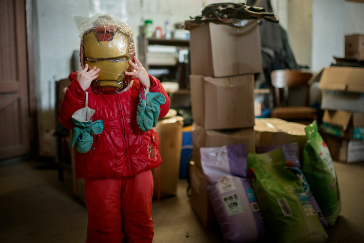 Alicia Esakov (three years old) tries on a Iron Man mask. She is the granddaughter of Irina and Alexei Esakov, who has founded the Pro-Russian emergency aid organization Dobrosvet. They store their collected aid in a worn out warehouse in the outskirts of Tallinn.