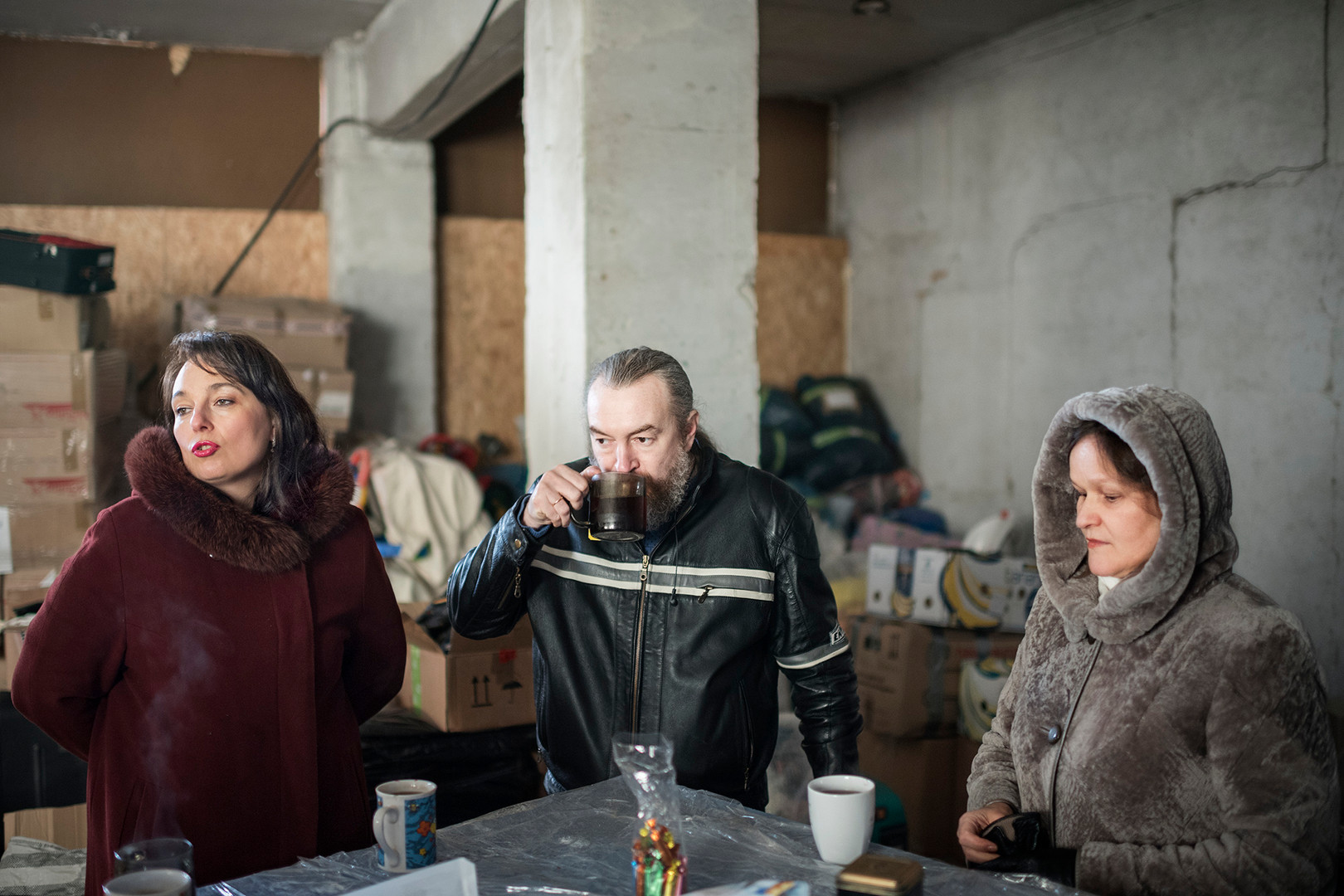 "Four years ago, Irina and Alexei (left and middle) founded the Dobrosvet. An organization, which collects emergency aid for the Pro-Russian Ukranians who are in need of medicine, clothing and food due to thethe civil war in the Ukrainian region of Donbass. With the help of the infamous Russian motorcycle gang The Night Wolves, Dobrosvet drives the emergency aid to Russia. From where it is transported southwards, across the border and to Lugansk, one of the main cities of the insurgency. ""I saw in Russian television how the war made it impossible for people in Donbass to live. They are also Russians, they are also our people. We need to help them, ""says Irina Esakov"