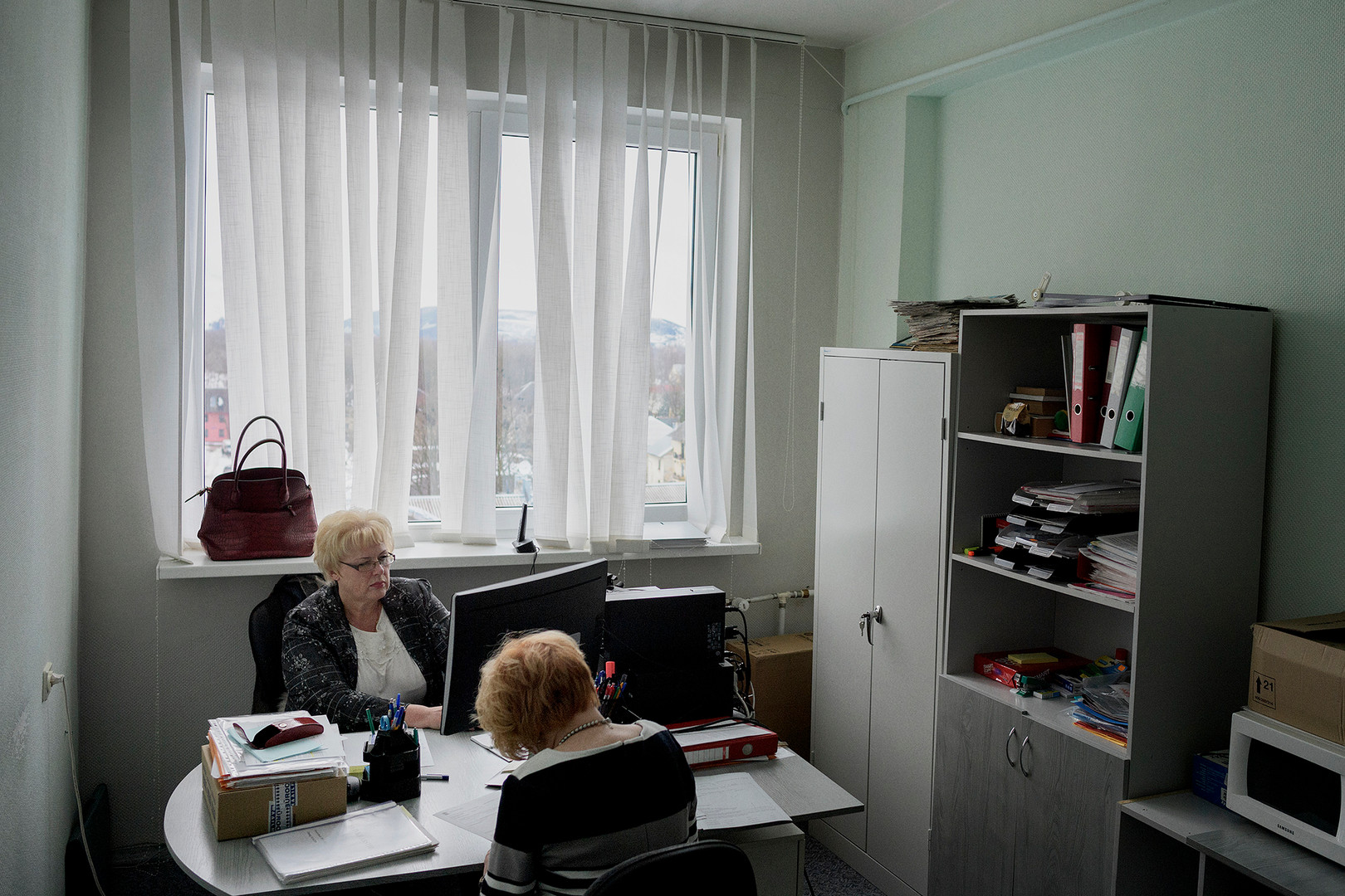 "Language inspectors Marge Mägi (front) Erika Lindsalva (back) in their 7th floor office in Kohtla-Järve. Their task is to check whether especially public employees, but also some private employees, speak Estonian. She and her employees go out and interview doctors, teachers and people working in the service industry, for example, waiters, and if they do not speak Estonian at a high enough level, they first get a warning and if nothing is being done they will see a fine. ""Estonia is a small country so it's vital that we keep our language. For hundreds of years we were under various rulings, so there is enormously much identity in our language. It is in the older generation, we have the problem and it dies at some point. Even though it's hard to think so. """
