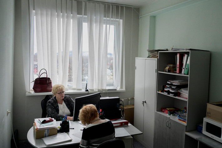 """Language inspectors Marge Mägi (front) Erika Lindsalva (back) in their 7th floor office in Kohtla-Järve. Their task is to check whether especially public employees, but also some private employees, speak Estonian. She and her employees go out and interview doctors, teachers and people working in the service industry, for example, waiters, and if they do not speak Estonian at a high enough level, they first get a warning and if nothing is being done they will see a fine. """"Estonia is a small country so it's vital that we keep our language. For hundreds of years we were under various rulings, so there is enormously much identity in our language. It is in the older generation, we have the problem and it dies at some point. Even though it's hard to think so. """""""