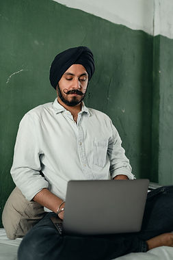 serious-young-man-using-laptop-while-sit