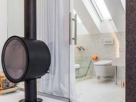 Итерьер ванной комнаты. Стеклянная ванна, стеклянная раковина, мебель и перегородка.