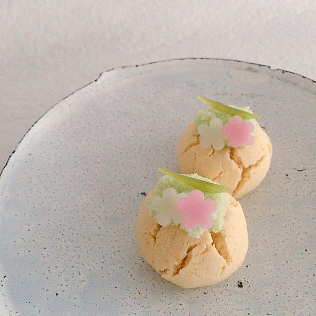 「小さな祈り」という銘の菓子。 第二十五候「螳螂生 (かまきりしょうず)」の時期、小さなカマキリが現れる頃。蕗の砂糖漬けを草にちょこんと乗るカマキリに見立てています。ピスタチオの黄身時雨にのせた、新しい味わいの和菓子です。