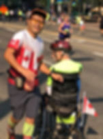 me ken thomas run wheeling in my three wheeled track wheelchair in a road race with my running guide Hiro  running beside me