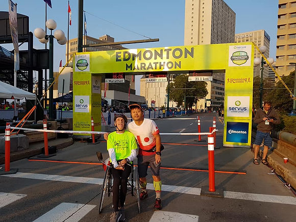 me and Hiro at the finish line with the Edmonton Marathon sign behind us