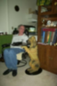 Me sitting in my livingroom swivel easy chair beside me is a table stand of a bludhound dog standing on his back legs holding a tray on which I put my remotes and beer mugs on