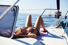 person sailing woman sunbathing on sailb