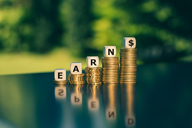 """Concept of earning and spending money. Dice form the word """"earn"""" placed on stacks of coins"""