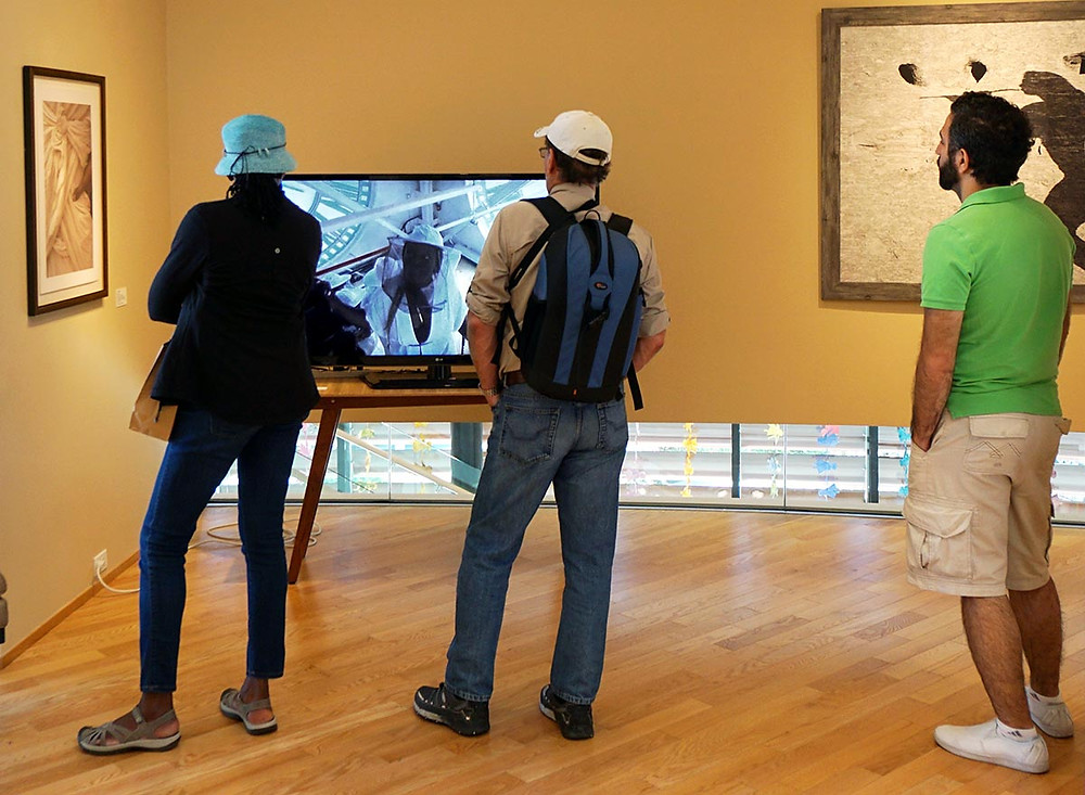 Visitors watch C. Davida Ingram's video art Procession, flanked by Linda Wolf's Boy Monk (left) and Heather Boose Weiss' Goddess.