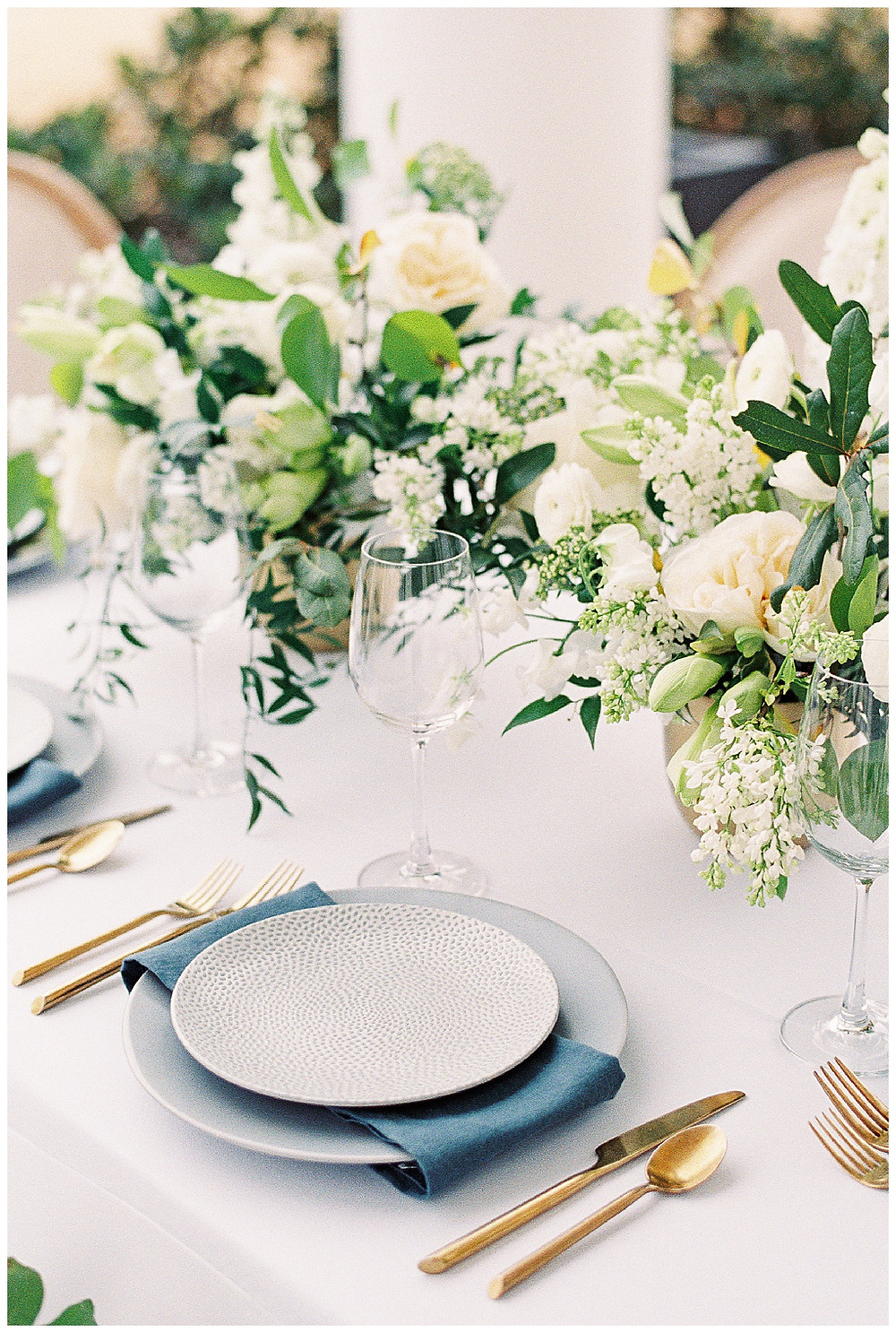 the pearl at sabine creek, blue plates, table set for six,  dallas wedding photography, dallas wedding, spring wedding, texas, floral installation, yellow, white, green, table scape with gold flatware, gold pots, white tablecloth , grey plates with texture, menus with deckled edges, gold silverware, styled flat lay, clear stemware, blue napkin