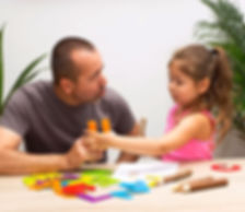 Hispanic fathe engaging his daughter in motor skill activties.