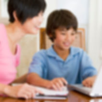 Asian adult helping a child with homework.