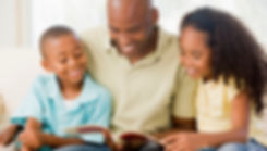 Black father reading with his children.