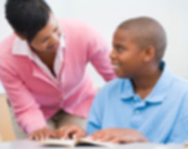 Young black student getting 1-on-1 help with studying from black female teacher.