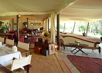 A traditional, authentic safari tent dining area in East Africa with silver service cutlery, wooden furniture & floor rugs.