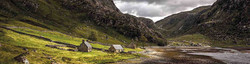 3 bothies', doubling a shooting lodges at the end of a Scottish sea loch, rocky mountain background.