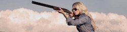 Pretty blonde girl with shotgun & shooting glasses, taking aim with blue sky & cloud background.