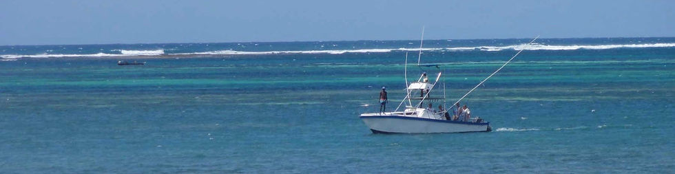 Malindi sea fishing boat with crew setting up outrigging lines for sailfish, close to shore, inside reef break.