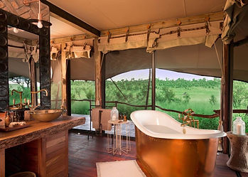 Classic traditional luxury tented safari camp wooden floor bathroom with view of Somalisa elephant pool in Hwange, Zimbabwe.