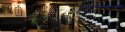 Restaurant kitchen cellar in sporting lodge with wine, champagne & sloe gin rack stacked on side.
